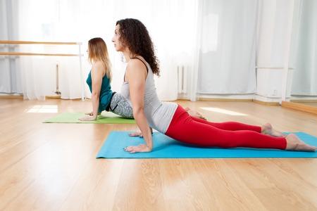 bhujangasana: Portrait of flexible yogini doing asana bhujangasana in yoga studio, cobra pose, yoga indoor