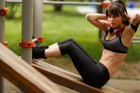 Athletic young brunette woman doing sit-ups exercising for her abdominal muscles oi street gym