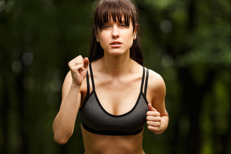 Closeup portrait of young beautiful woman brunette in motion, while Jogging outdoors. Concept of sport and healthy lifestyle Stock Photo
