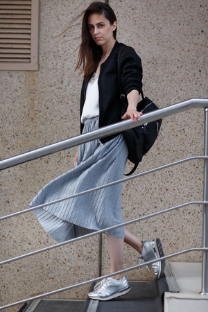 bajando escaleras: Brunette young woman in grey skirt and black jacket walks down stairs in sneakers and with bag