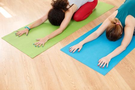 floor mat: Two young caucasian women practicing yoga on floor mat in class