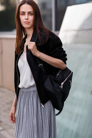 Brunette young woman holding on shoulder large black bag and looking directly at camera