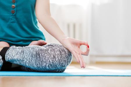 Yoga meditation in light room, woman sitting lotus position, hands closeup Stock Photo