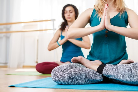 coupled: Closeup portrait in gym of two young women sitting in lotus position with hands coupled