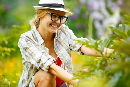 headress: blonde woman in glasses and hat in garden on background of plants