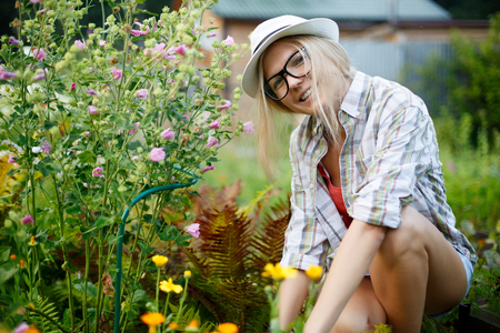 smiling girl in glasses and hat sitting next flowers in garden Stock Photo