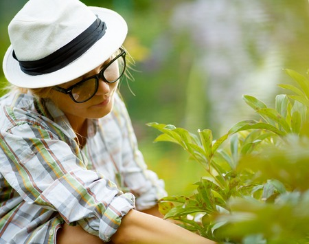 headress: young blonde female with glasses and hat touching plants