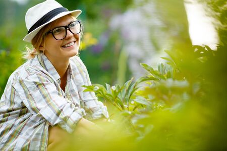 headress: blonde woman in hat on background of plants Stock Photo
