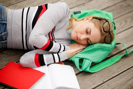 repose: blonde with glasses and textbooks is sleeping on wooden floor Stock Photo