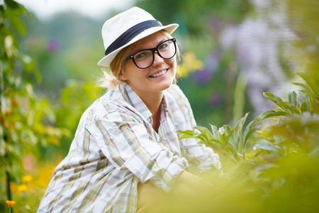 blak and white: blonde girl in black glasses on background of plants in garden Stock Photo