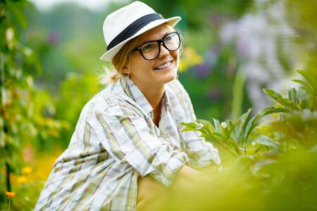 gente adulta: young girl in black glasses on background of plants and flowers
