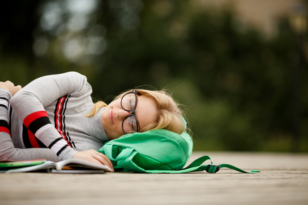 textbooks: tired student spectacled fell asleep for textbooks in yard Stock Photo