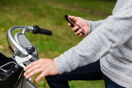 road position: Male figure on the bike with smartphone, portrait on summer day