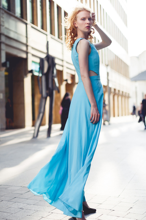 woman in long blue dress in front of building in city Stock Photo
