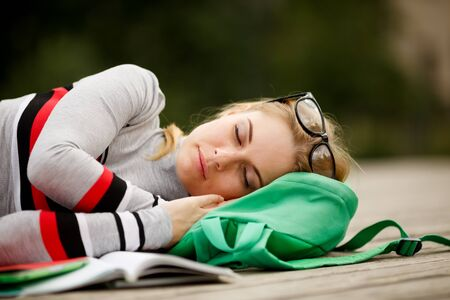 young blonde is sleeping on wooden stage in College yard