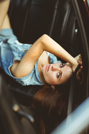tinted: Girl with long hair lying on leather seat of car. tinted photo
