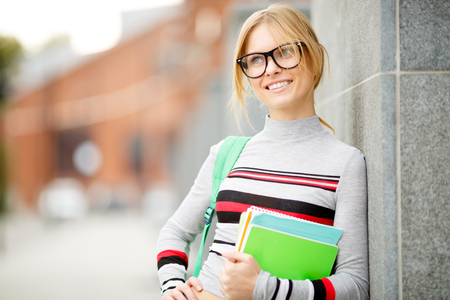young student with books near wall of building Stock Photo