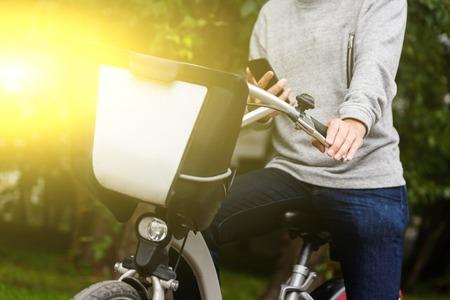 Mann in Freizeitkleidung sitzt auf seinem Fahrrad mit Handy im grünen Bereich. Bild mit Lens Flare Effekt