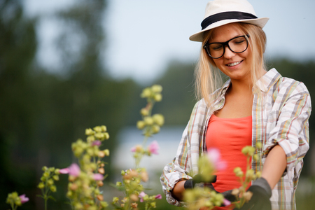 smiling blonde girl with gloves care for floral bushes