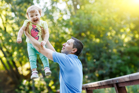 Dad holds baby daughter in his arms in summer park.Image with lens flare effect Stock Photo