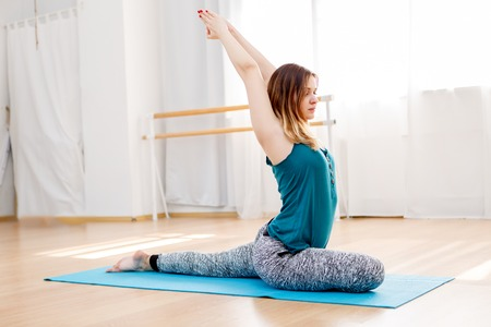 eka: Beautiful caucasian girl doing yoga exercises indoor, pigeon asana, Eka Pada Rajakapotasana