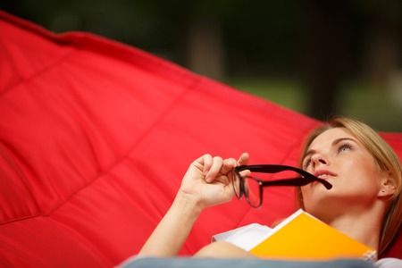 Girl reclining with glasses in hammock , close-up