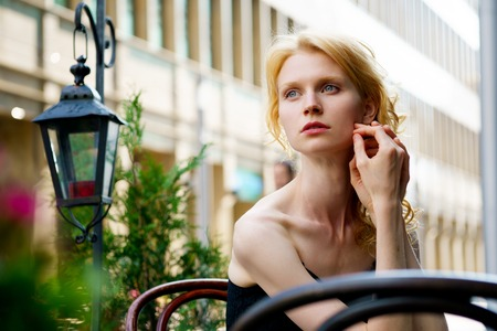 femal: Beautiful blond woman waiting at a table in a cafe, outdoors, looking sideways