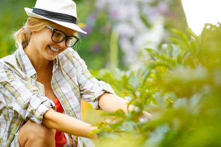 headress: smiling young blonde woman in glasses and hat in garden Stock Photo