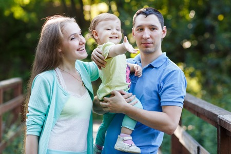 jardin de infantes: Young parents with daughter on hands in park on bridge