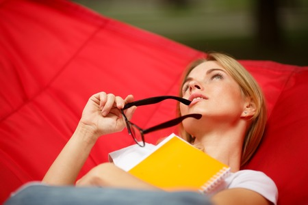 Dreamy girl with glasses in hands lies in red hammock