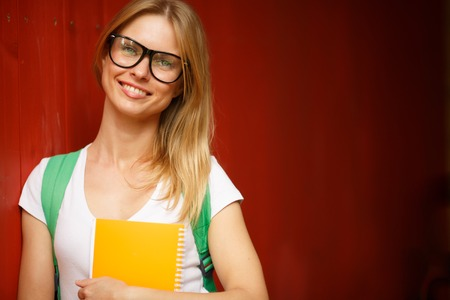 spectacled: Girl in glasses smiles amid Burgundy wooden wall blurred background