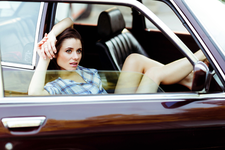 smiley face car: Brunette with long legs sitting in car with window open, tinted photo