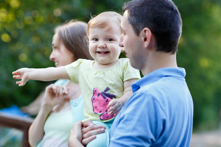 Happy family with little daughter on bridge in summer park Stock Photo