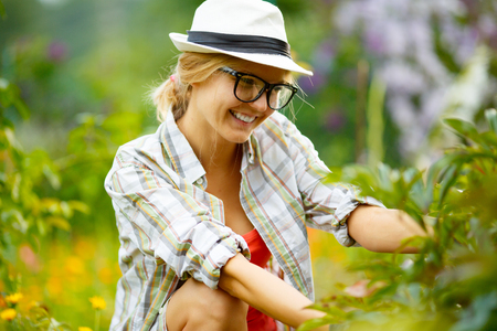 headress: young woman in glasses and hat in garden on background of plants
