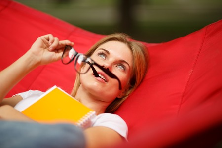 Girl with notebook and glasses resting on red hammock Stock Photo