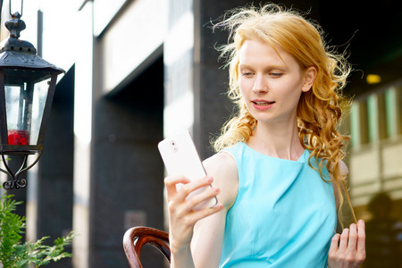 Portrait of young blond woman sitting in cafe and using modern white smartphone Stock Photo