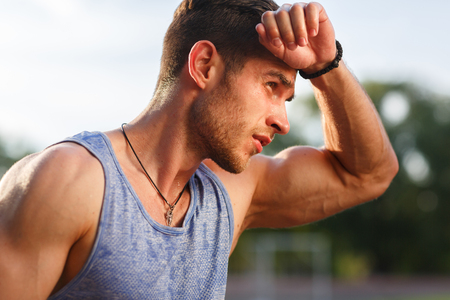 Portrait of fatigued fitness guy after exercises on hot sunny day Stock Photo