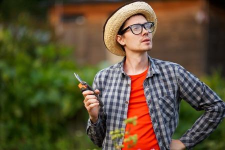 Gardener jeune homme dans un chapeau et des lunettes tenant voilages d'élagage