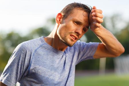 ejercicio cansado y hombre deportivo de calor secándose el sudor de la cara. Retrato en el fondo la naturaleza