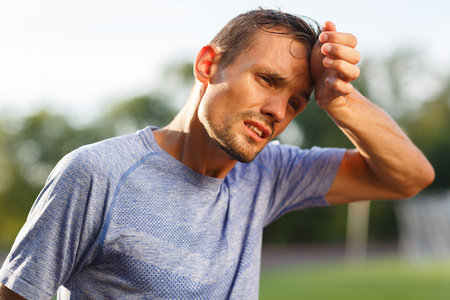Tired exercise and heat sporty man wiping sweat from his face. Portrait on nature background Stock Photo