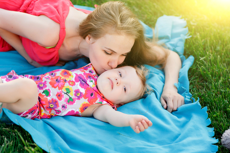 niños sanos: Young mother kissing little girl lying on blue blanket on lawn in park