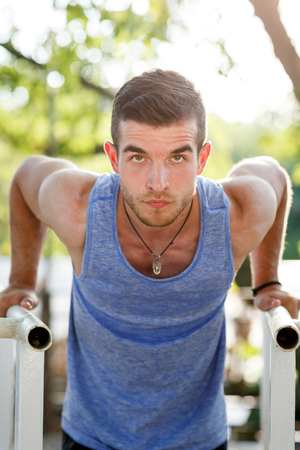 pullups: Closeup portrait of fit man doing pull-ups on crossbars in park Stock Photo