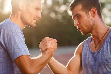 tense: Two handsome strong athlete tense men handshake outdoors. Image with lens flare effect