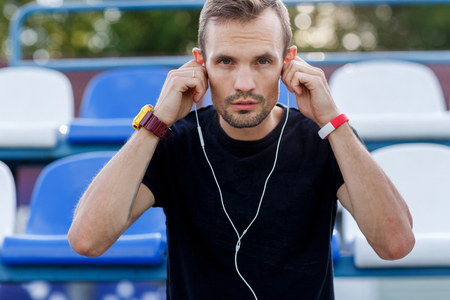 Sporty man putting headphone in his ears before jogging outdoors