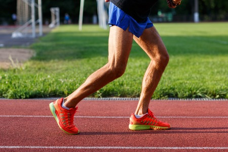 cross legs: Muscular legs of men in shorts and sports shoes on running track at street stadium