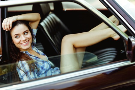 smiley face car: Smiling brunette in car with window open, tinted photo