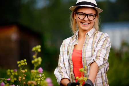 backyard woman: Cute caucasian young woman gardener in hat and glasses posing in backyard on summertime Stock Photo
