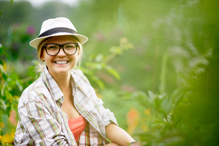 Young caucasian smiling woman caring for plants in her garden and looking at camera