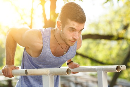 crossbars: Fitness young man training on parallel crossbars. Image with lens flare effect Stock Photo