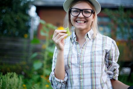 Portrait of cheerful young girl in hat with leaf in hands in the village Stock Photo